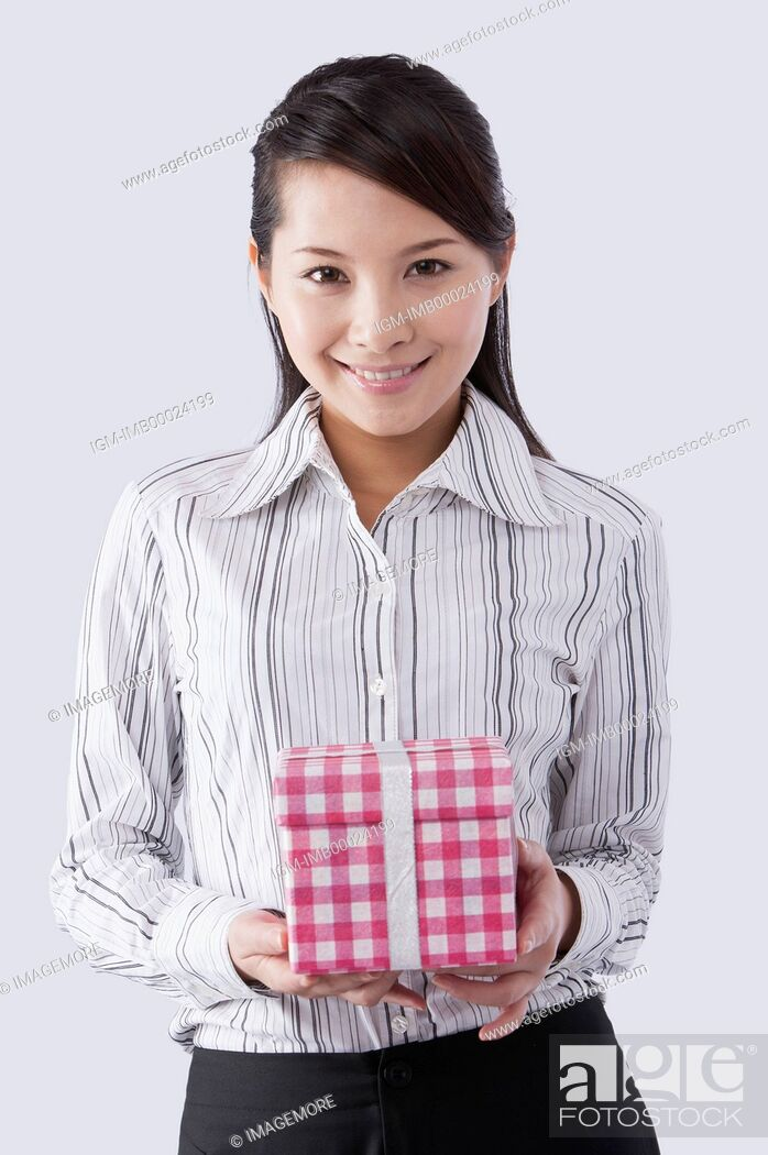 Imagen: Young business woman holding a gift and smiling at the camera,.