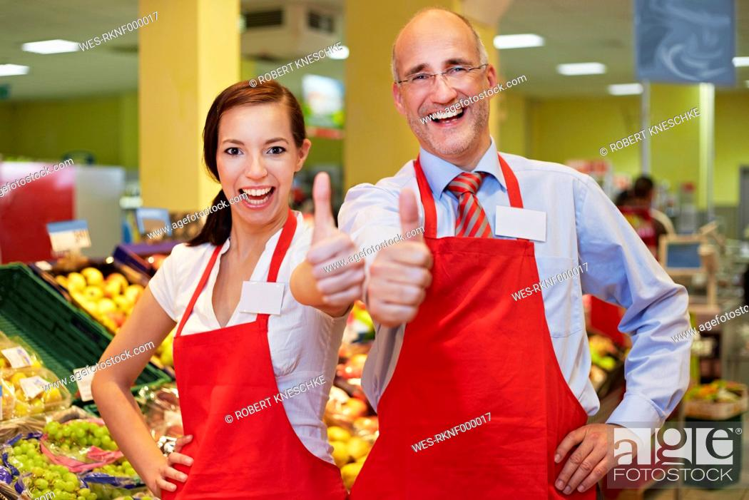 Stock Photo: Germany, Cologne, Man and woman in supermarket showing thumbs up, smiling, portrait.