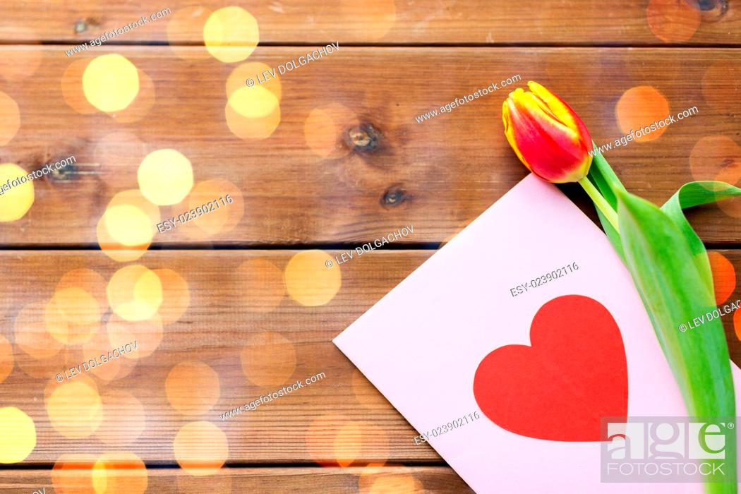 Stock Photo: holidays, love and valentines day concept - close up of tulip flowers and greeting card with heart on wooden table.