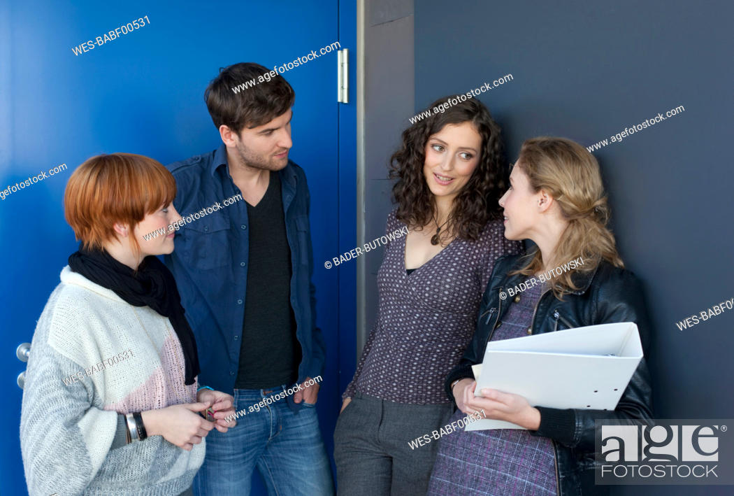 Stock Photo: Germany, Leipzig, University students talking and discussing together in university.
