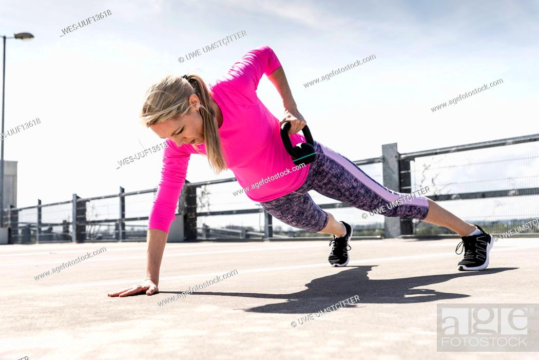 Stock Photo: Woman training with dumbells, doing one-armed plank.