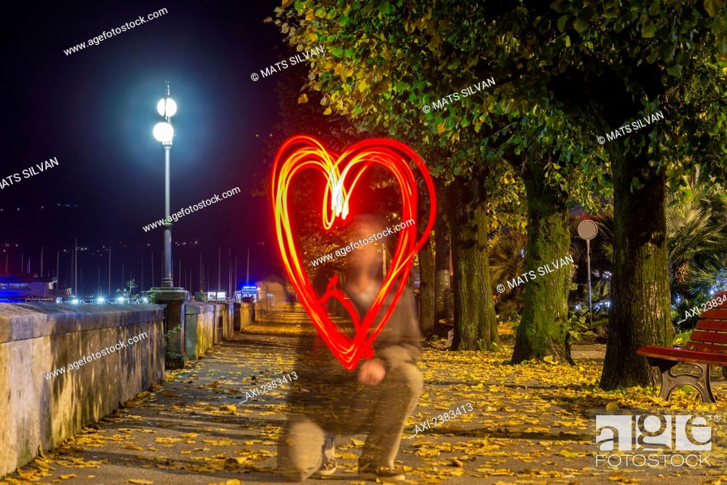 Stock Photo: A man drawing a red glowing heart shape in the air; Locarno, Ticino, Switzerland.
