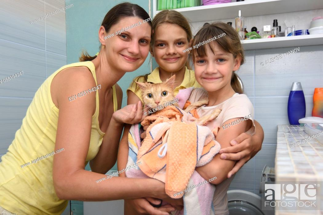 Stock Photo: Family poses in the bathroom with wet bathed cat wrapped in towel.