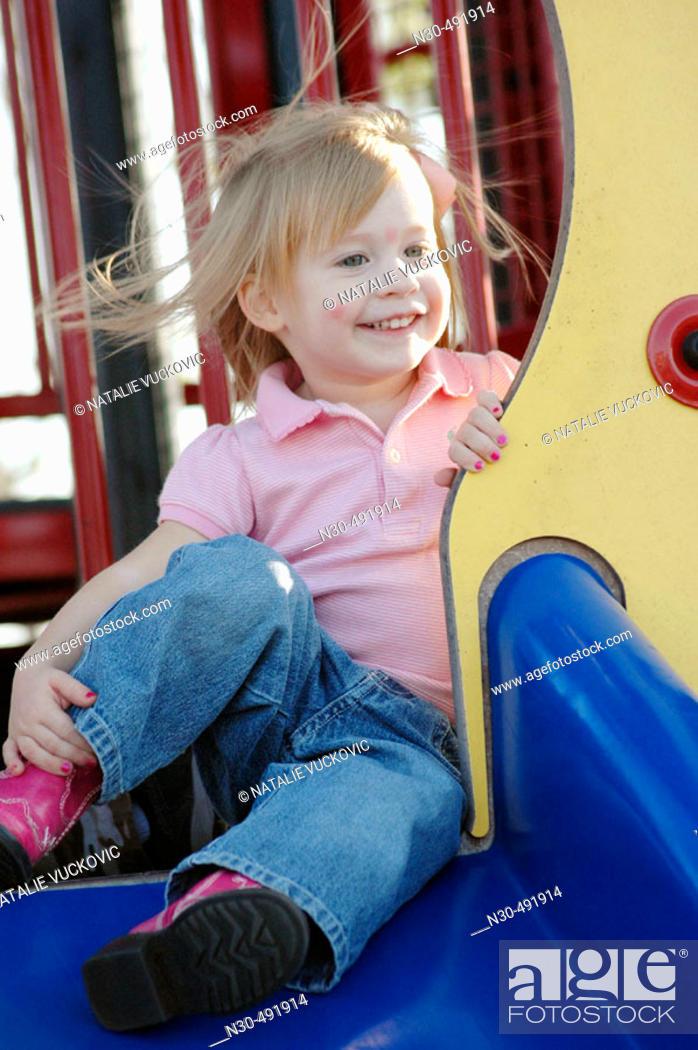 Stock Photo: 3 year old girl on slide.