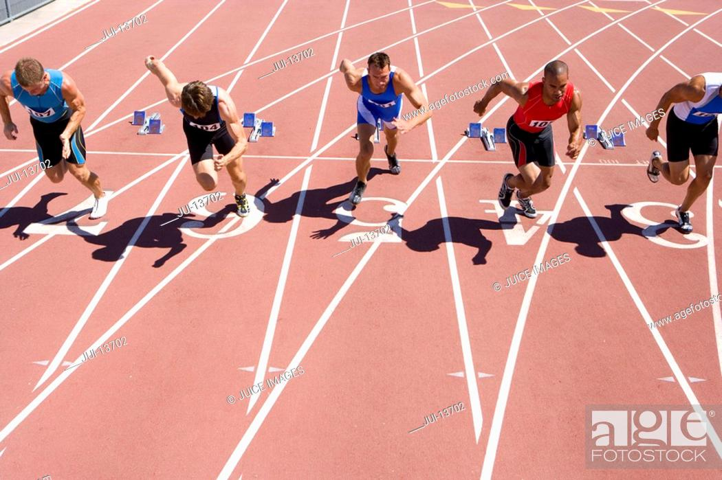 Stock Photo: Male sprinters leaving starting blocks, elevated view.