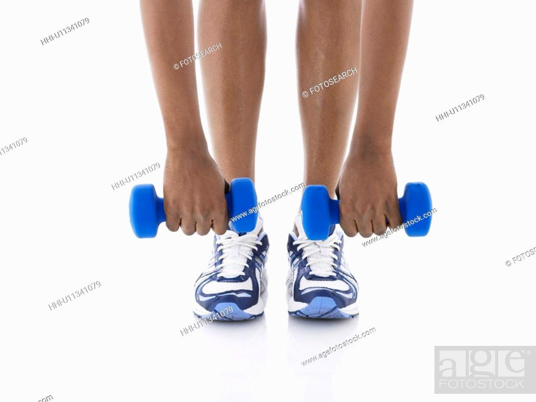 Stock Photo: Woman lifting dumbbells (low section).