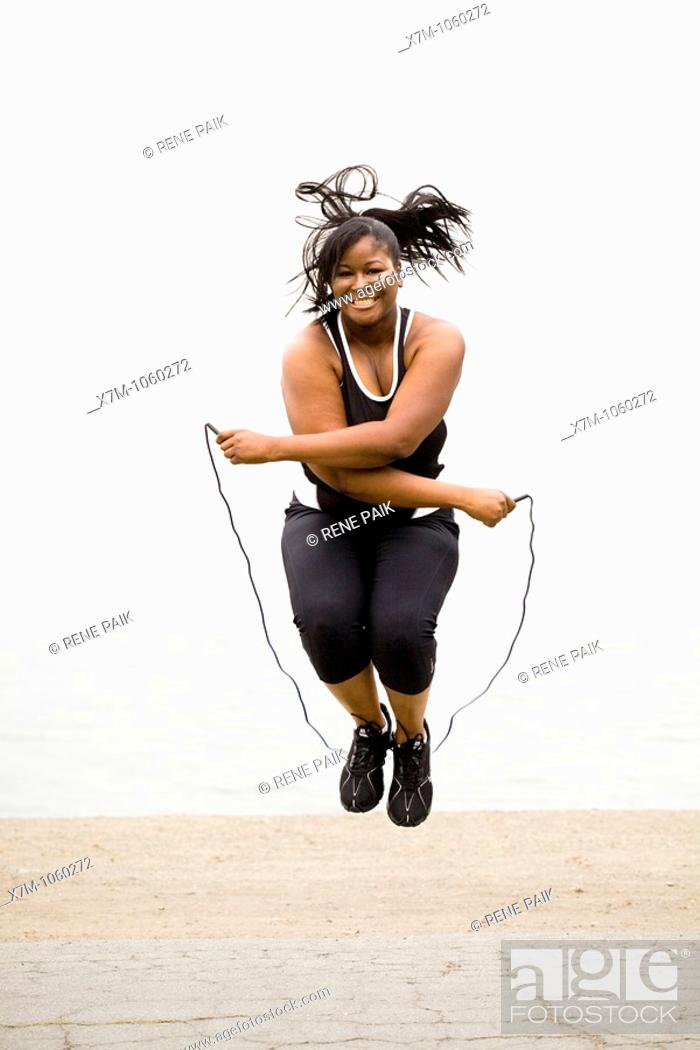 Stock Photo: Plus size model jumping rope at a marina park.