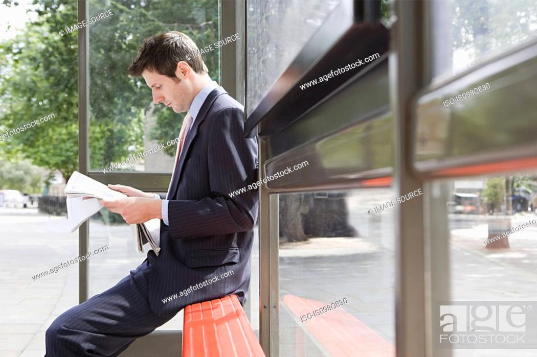 Stock Photo: Businessman reading newspaper at bus stop.
