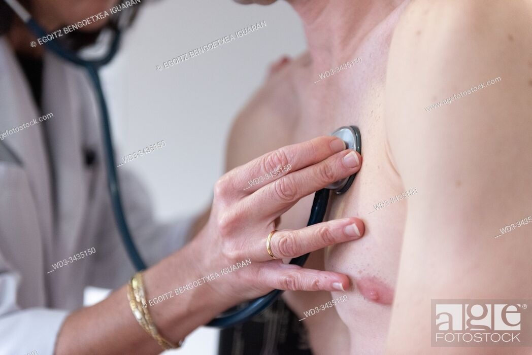 Photo de stock: A female doctor checking the heart health of a man with a stethoscope.