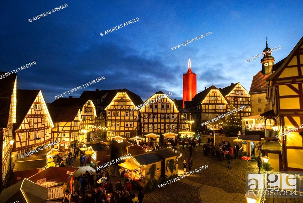 Stock Photo: dpatop - The world's largest candle shines at the Christmas market in Schlitz, Germany, 02 December 2017. A 36 metre high stone tower is wrapped in a red cloth.