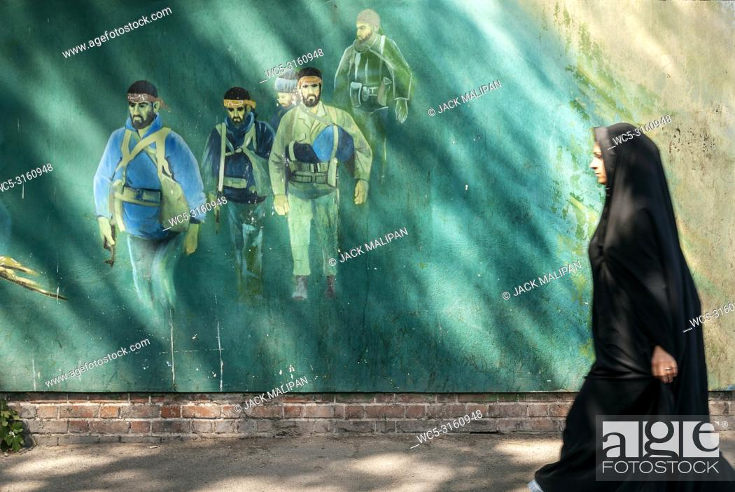 Imagen: veiled muslim woman walking by revolutionary fighters mural in downtown tehran city street iran outside old US american embassy.