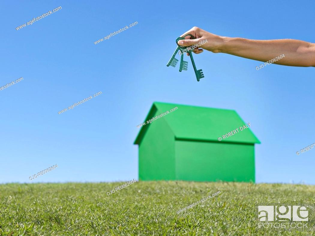 Stock Photo: Hand holding green keys over small model house.