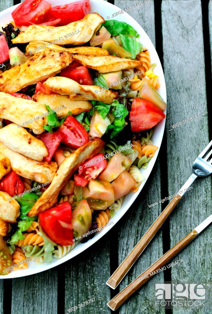 Photo de stock: Pasta salad with tomato and chicken on wooden table view from above.