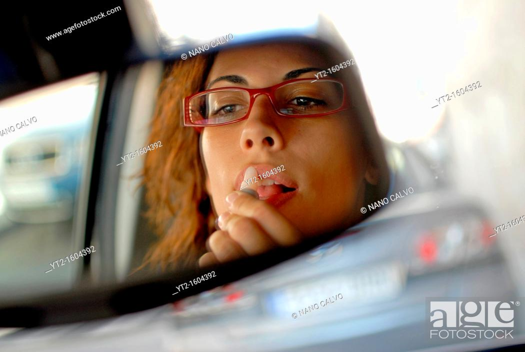 Stock Photo: Young woman paints her lips in her car.