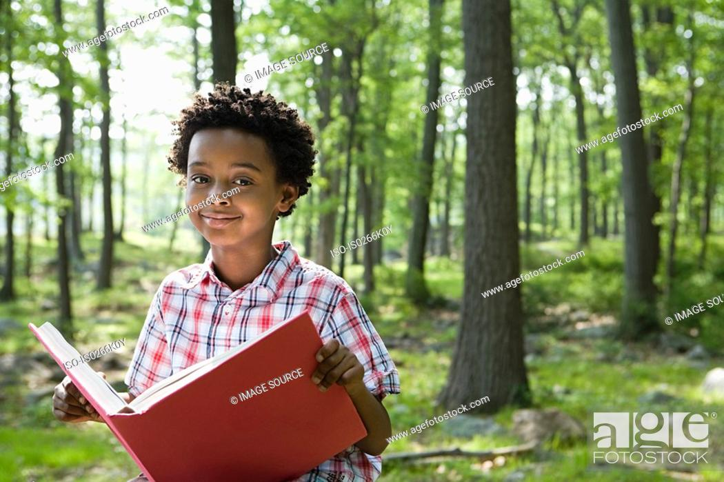 Stock Photo: A boy holding a book.