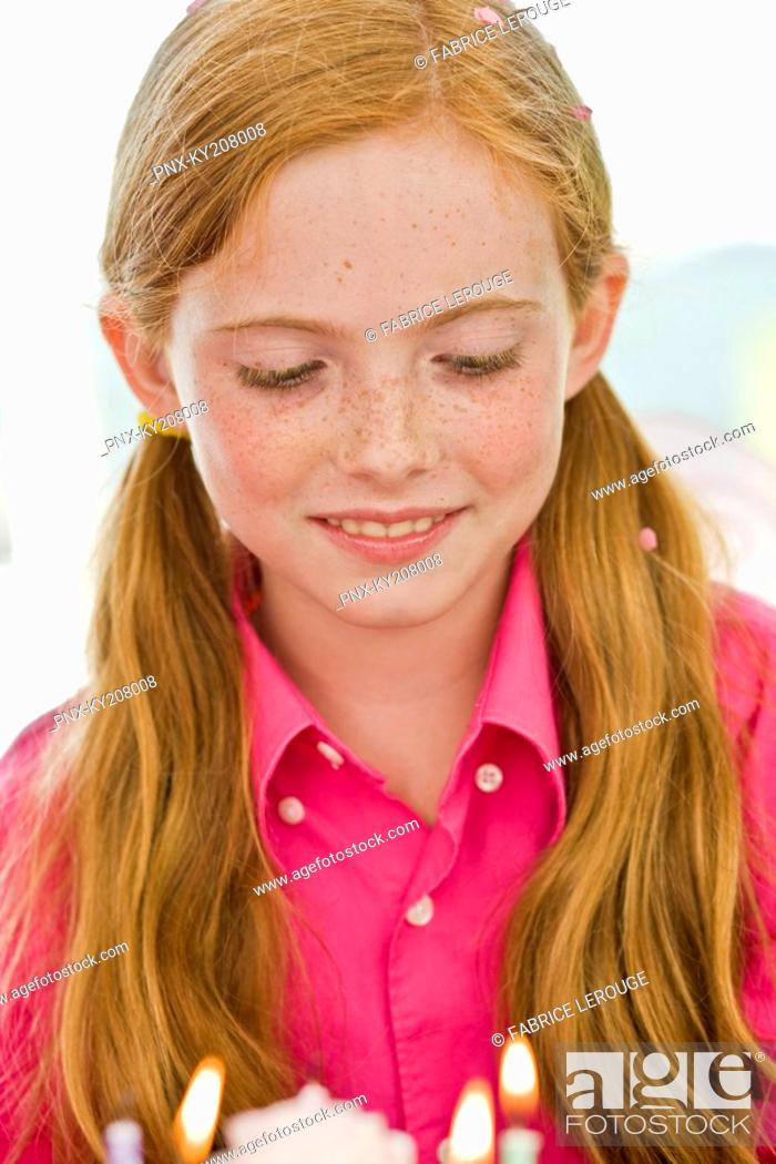 Stock Photo: Close-up of a girl looking at a birthday cake.