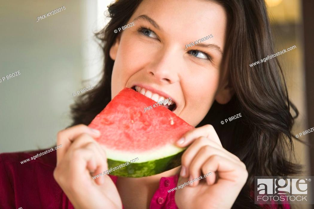 Stock Photo: Woman eating a watermelon slice.