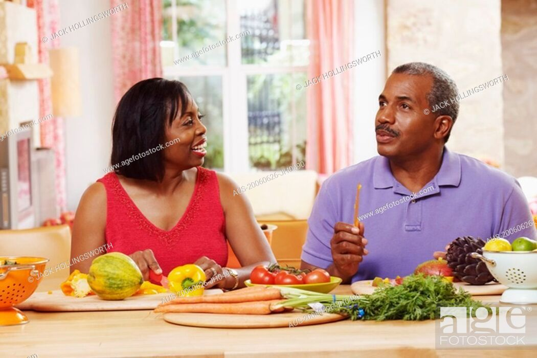 Stock Photo: Mature couple cutting vegetables and talking.