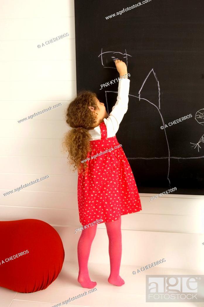 Stock Photo: Girl drawing on a blackboard.