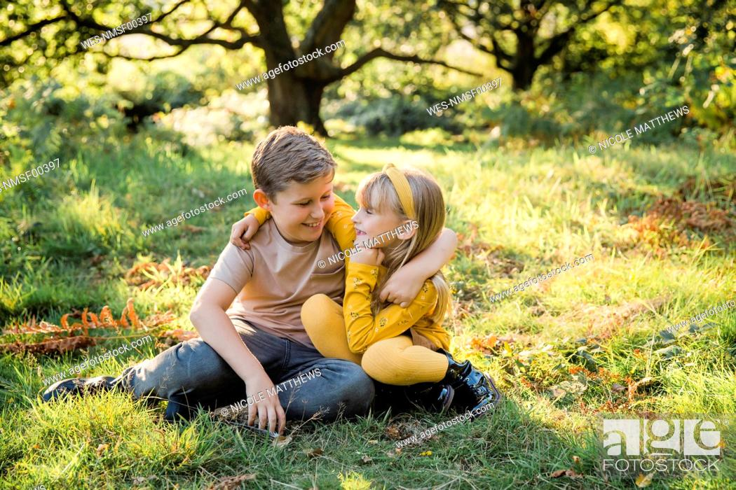 Stock Photo: Portrait of happy little girl arm in arm with her older brother on a meadow.