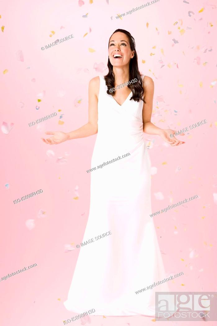 Stock Photo: Bride standing beneath falling confetti.
