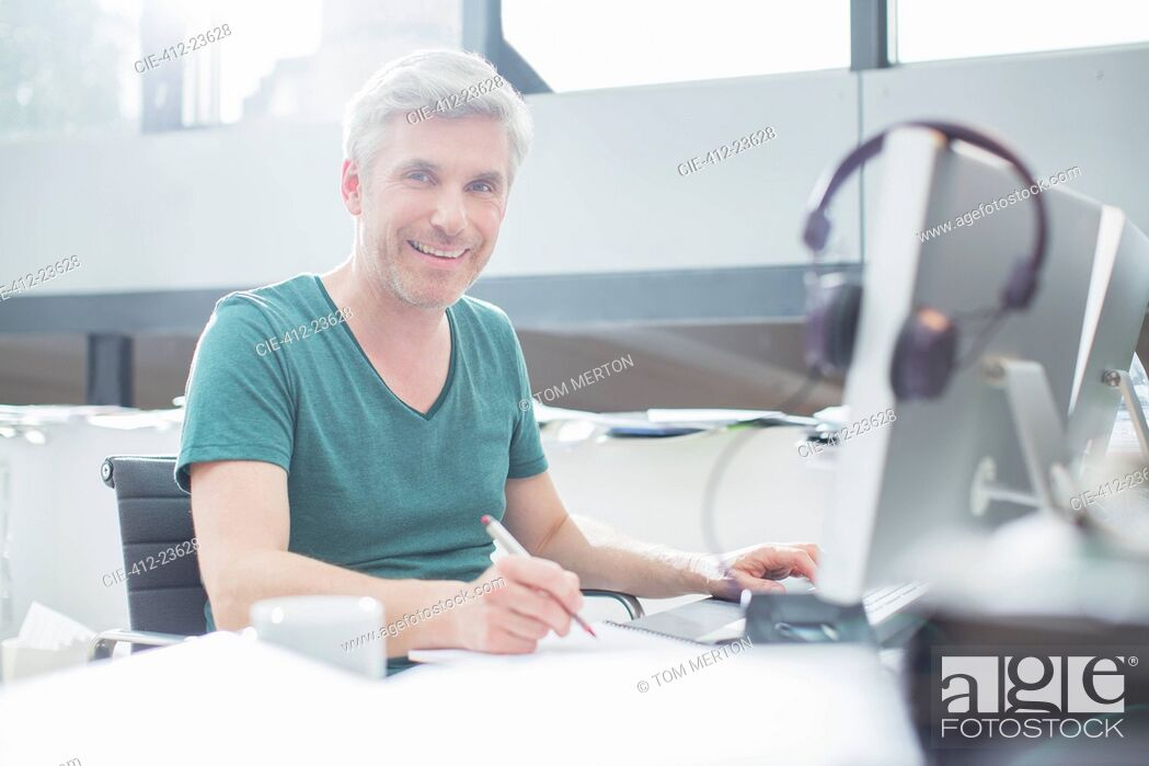 Stock Photo: Older man working on computer at desk.