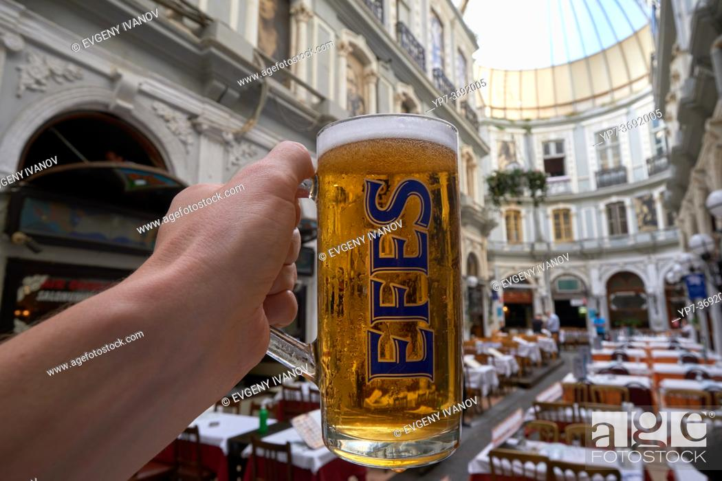 Stock Photo: Male hand holding Efes beer glass in Cicek Pasaji, Istanbul, Turkey.