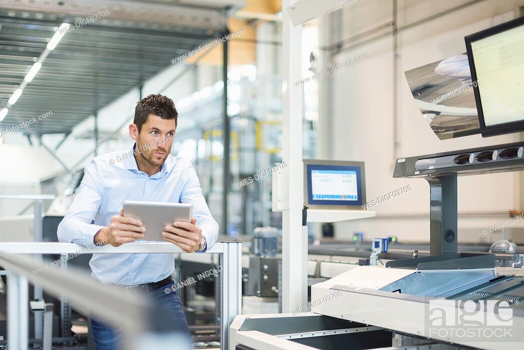 Stock Photo: Businessman with tablet looking at machine in modern factory.