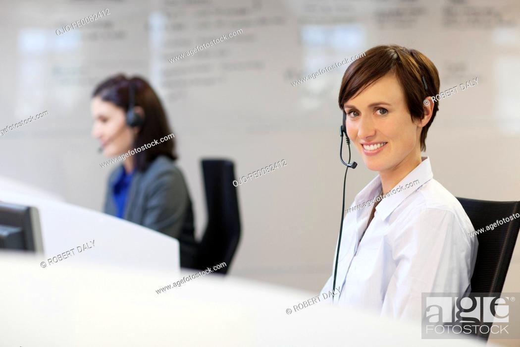 Stock Photo: Portrait of smiling woman wearing headset.