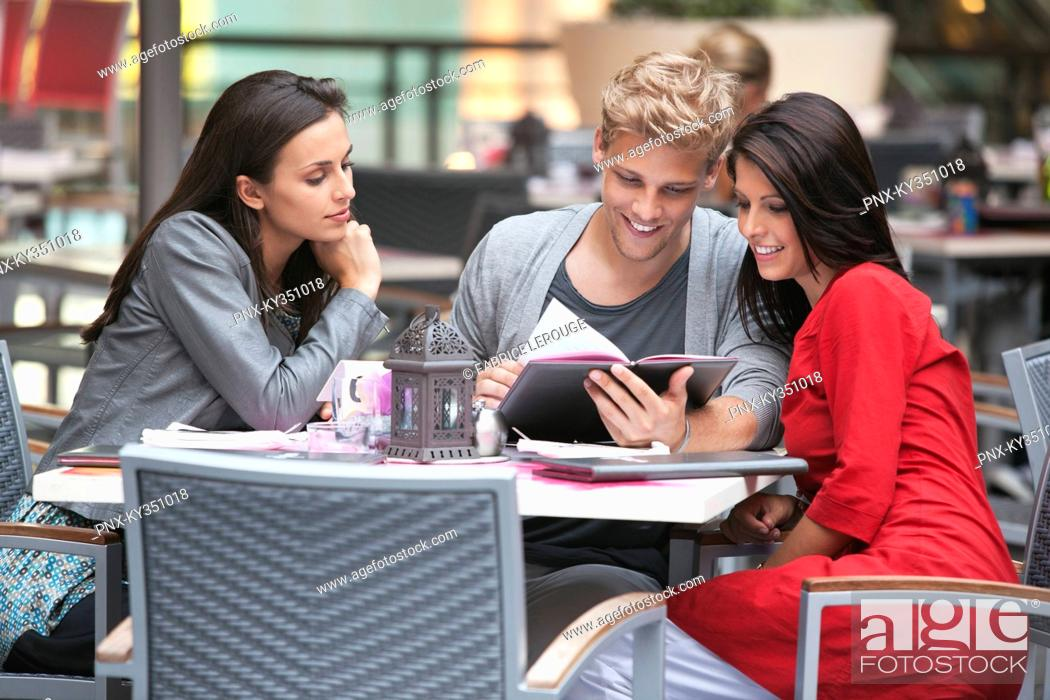 Stock Photo: Young man with two young women looking at menu in a restaurant.