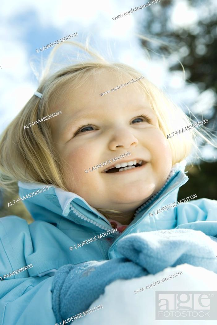 Stock Photo: Toddler girl in snow, close-up, portrait.