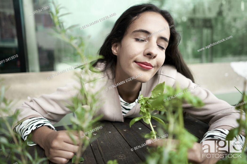Imagen: joyful woman smelling fresh thyme and basil plants.