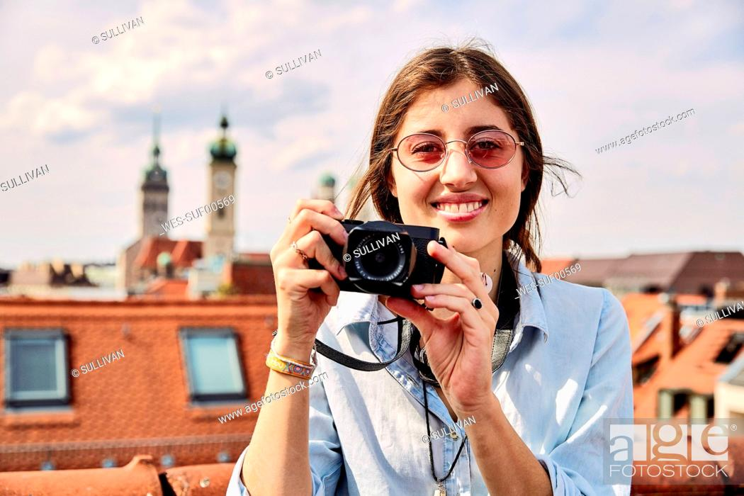 Stock Photo: Young smiling woman taking picture.