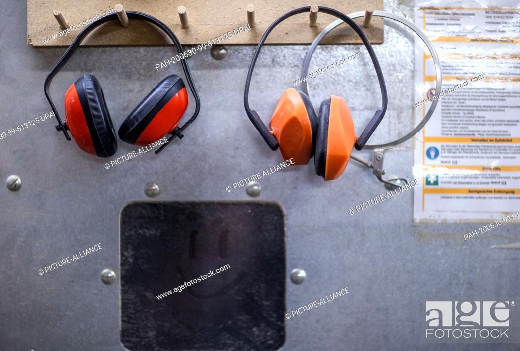 """Stock Photo: 22 June 2020, Mecklenburg-Western Pomerania, Rostock: Hearing protectors to protect against machine noise are hanging in the workshop """"""""Historical keyboard."""