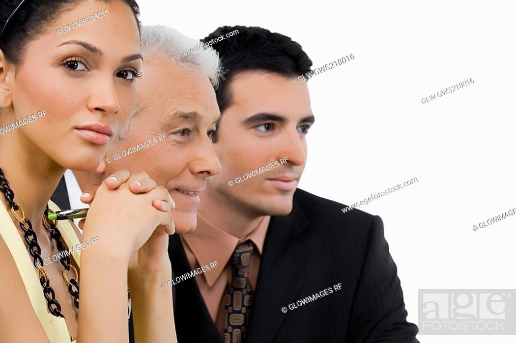 Stock Photo: Two businessmen and a businesswoman at a meeting in a conference room.