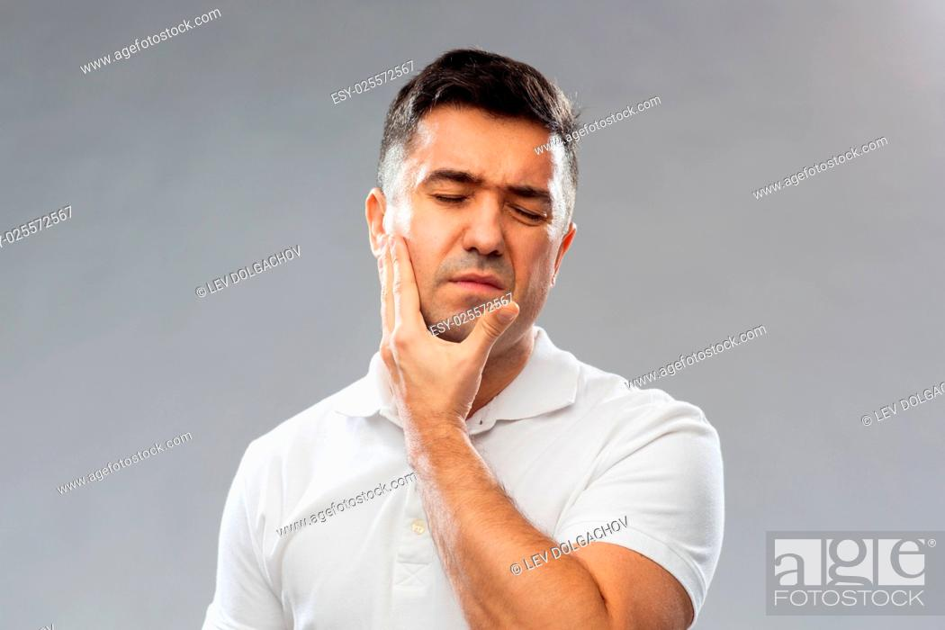 Stock Photo: people, healthcare, dentistry and problem concept - unhappy man suffering toothache over gray background.