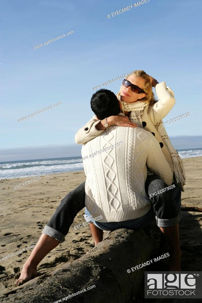 Stock Photo: Young couple hugging at beach in winter.