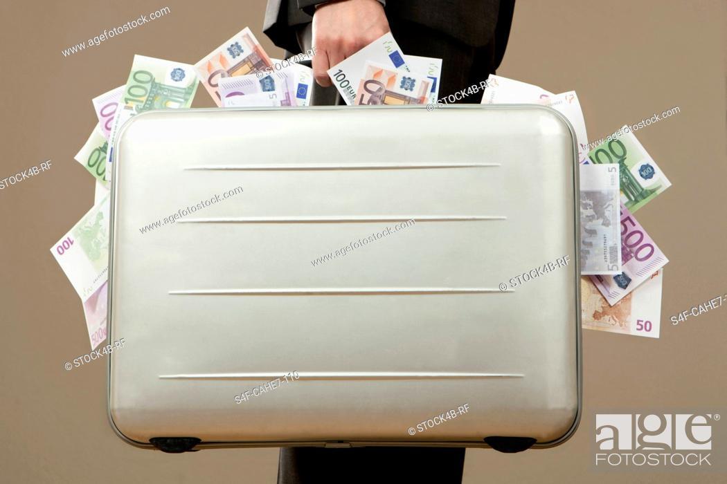 Stock Photo: Businessman holding suitcase full of Euro notes.