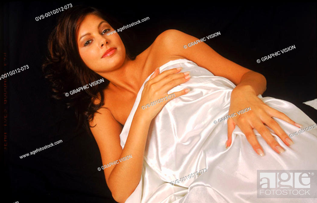 Stock Photo: Portrait of young woman lying down covered with a bed sheet.