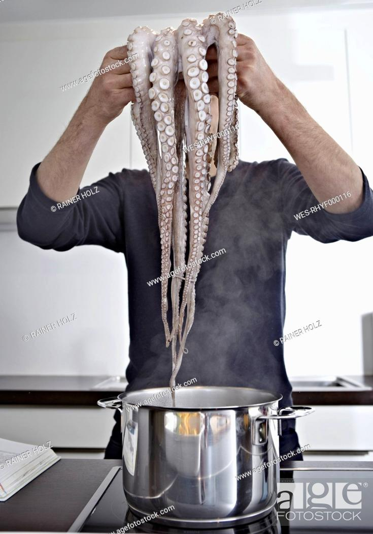 Stock Photo: Germany, Cologne, Mid adult man cooking octopus in kitchen.