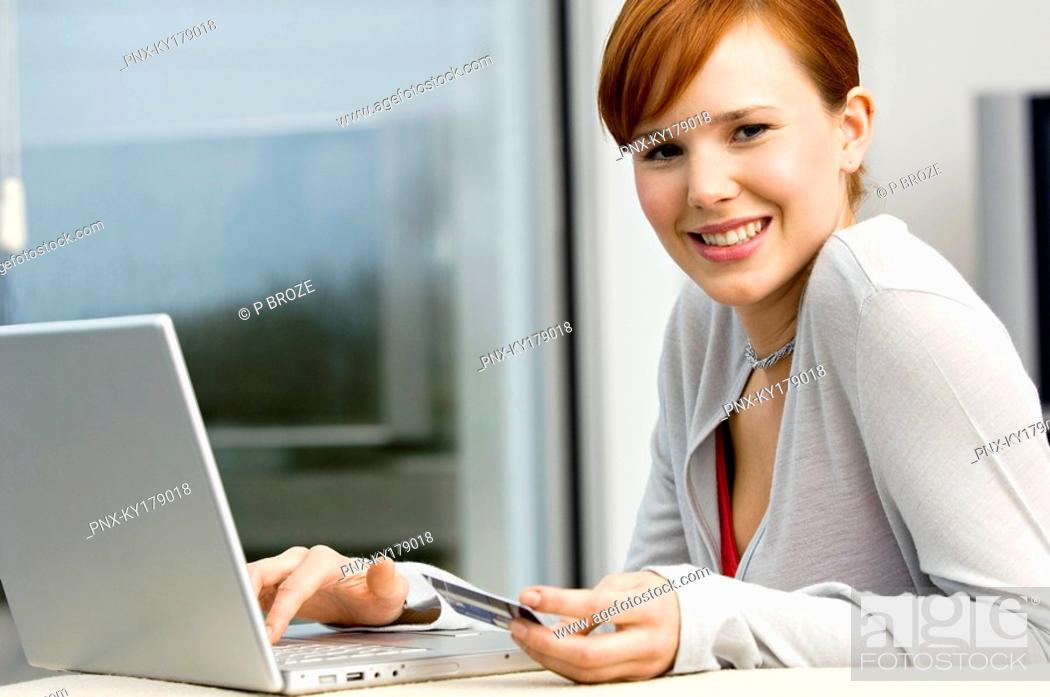 Stock Photo: Portrait of a young woman holding a credit card and using a laptop.