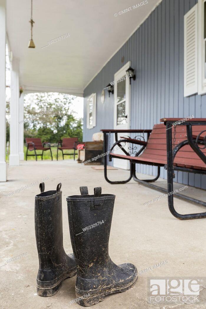 Photo de stock: Dirty wellingtons on front porch.