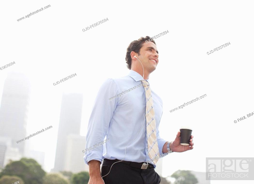 Stock Photo: Businessman listening to headphones and carrying coffee.