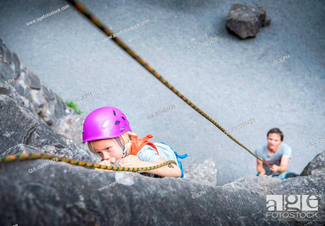 Stock Photo: Boy wearing climbing helmet rock climbing.