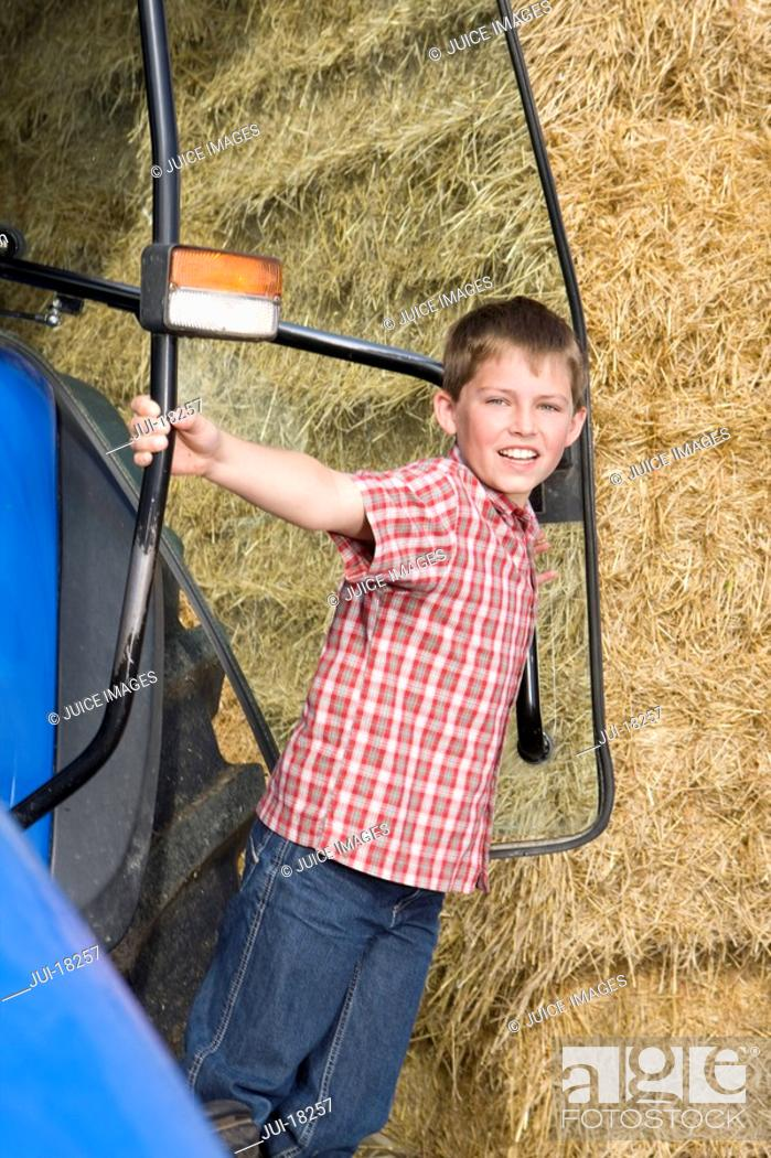 Stock Photo: Portrait of boy leaning outside tractor next to hay.