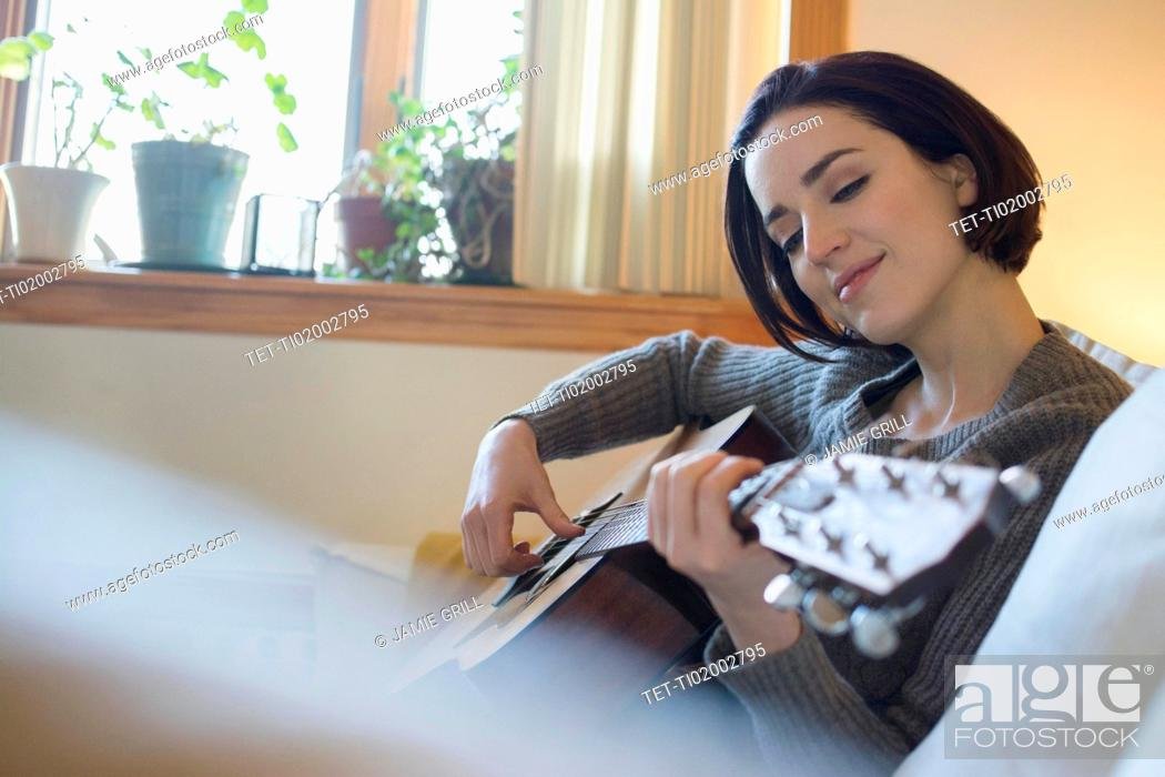 Stock Photo: Woman playing guitar at home.