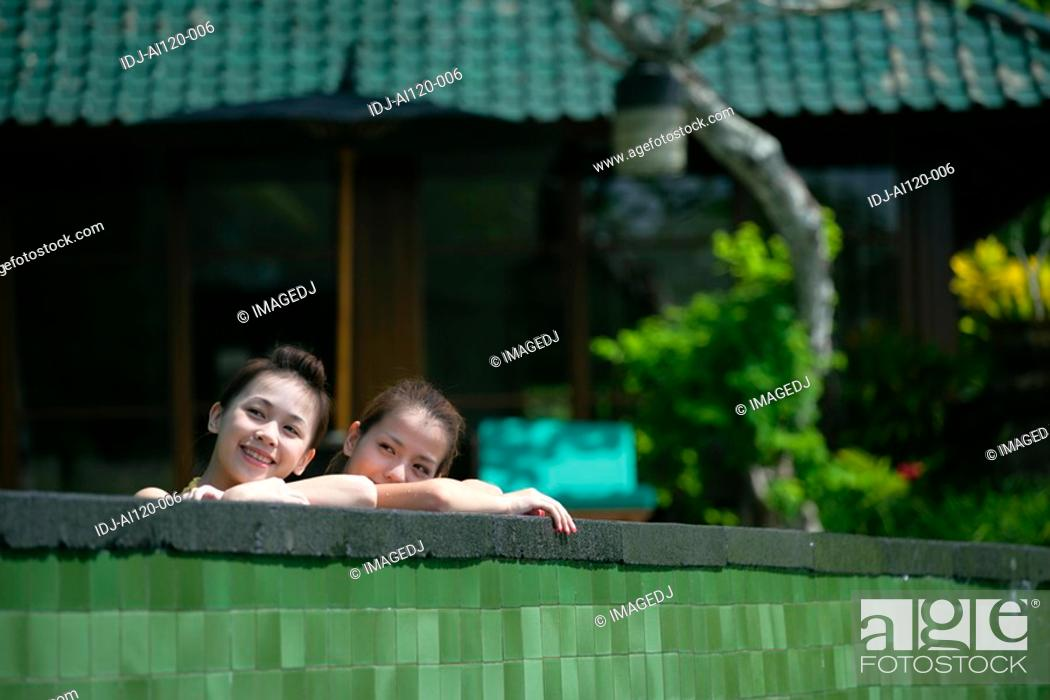 Stock Photo: Two teenage girls leaning near boundary wall.