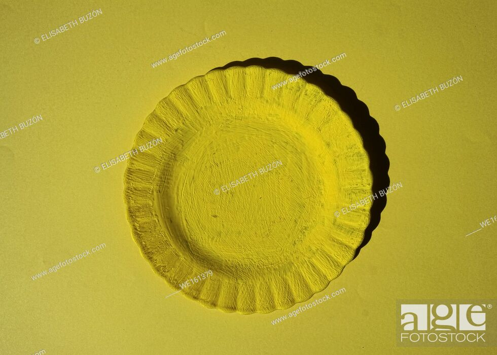 Stock Photo: Yellow plate on yellow background.