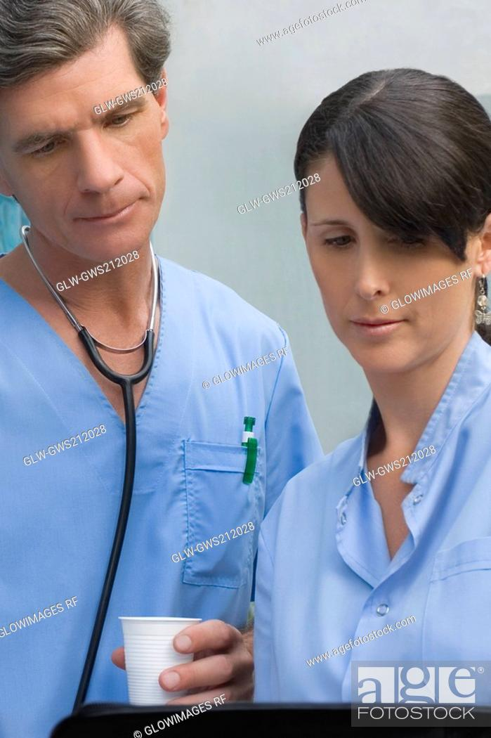 Stock Photo: Male surgeon and a female surgeon looking at a medical record.