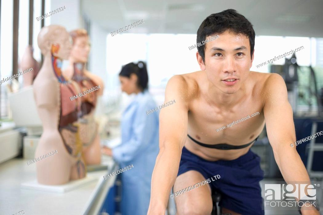 Stock Photo: Asian man riding stationary bicycle in laboratory.
